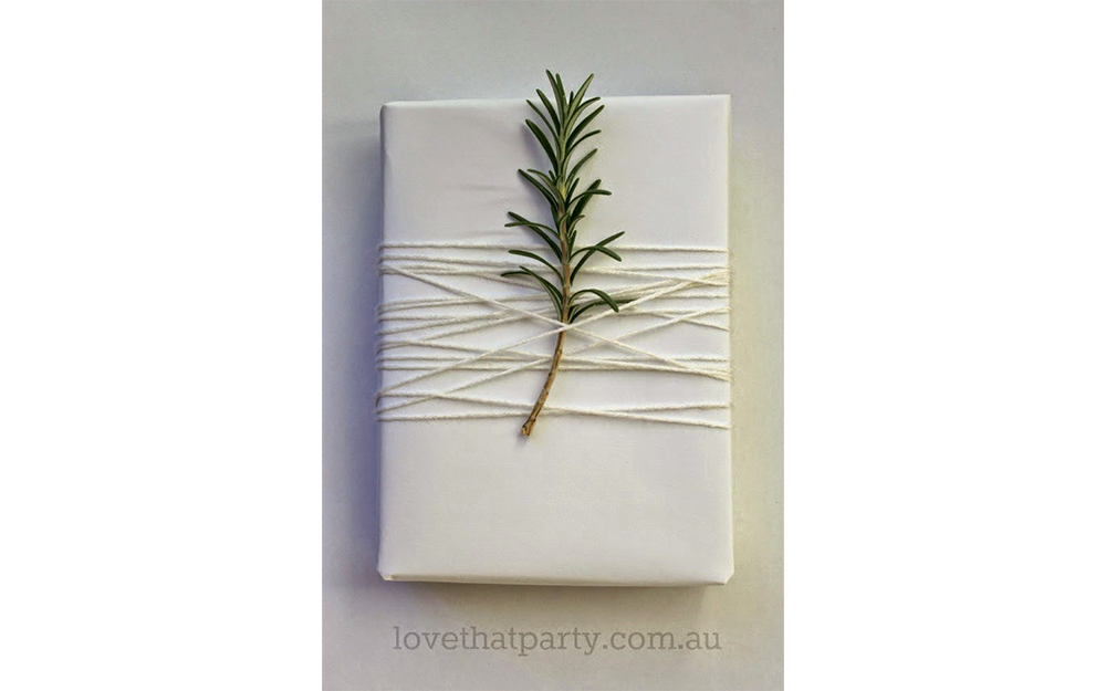White present wrapped with white twine and a small fir branch