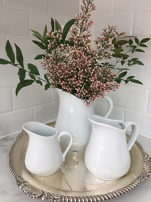 Three white pitcher vases with flowers